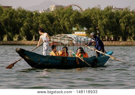 Kunming China - April 24 2006: Tourists on a sightseeing boat paddled by two boatman using wide wooden paddles on Dianchi Lake in Daguan Park