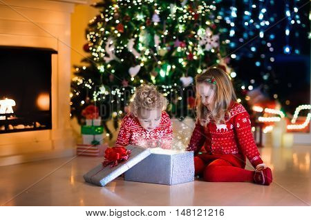 Family on Christmas eve at fireplace. Kids opening Xmas presents. Children under Christmas tree with gift boxes. Decorated living room with traditional fire place. Cozy warm winter evening at home. poster
