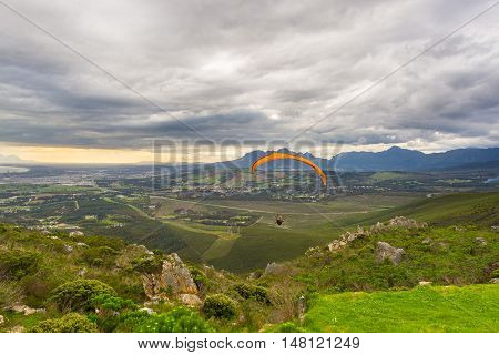Paraglider flying over the green mountains around Cape Town South Africa. Winter season cloudy and dramatic sky. Unrecognizable people.