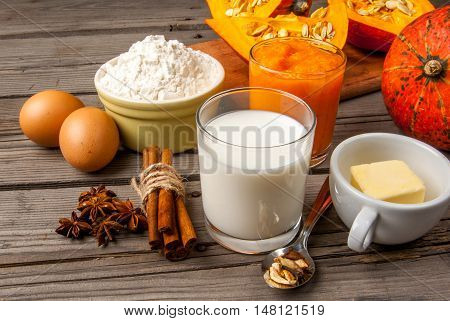 Selection of ingredients for making a traditional pumpkin pie for Thanksgiving or Halloween. At the rustic wooden table, copy space