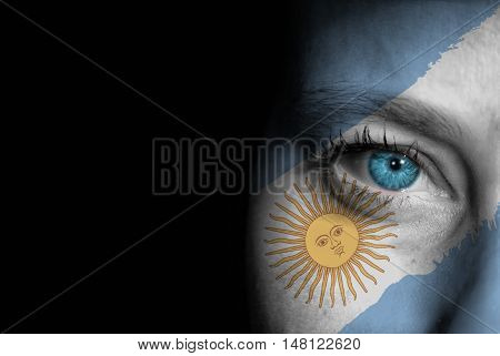 A young female with the flag of Argentina painted on her face on her way to a sporting event to show her support.