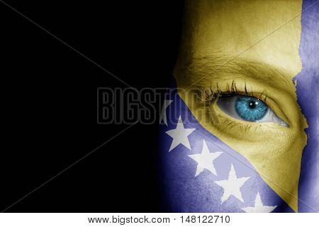 A young female with the flag of Bosnia and Hercegovina painted on her face on her way to a sporting event to show her support.