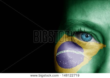 A young female with the flag of Brazil painted on her face on her way to a sporting event to show her support.