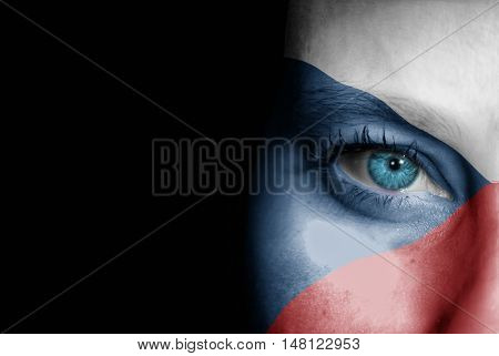A young female with the flag of Czech Republic painted on her face on her way to a sporting event to show her support.