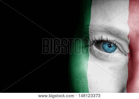 A young female with the flag of Italy painted on her face on her way to a sporting event to show her support.
