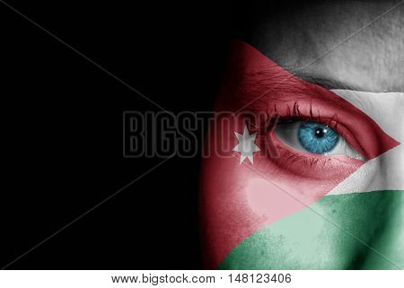 A young female with the flag of Jordan painted on her face on her way to a sporting event to show her support.