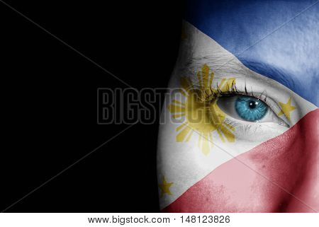 A young female with the flag of Philippines painted on her face on her way to a sporting event to show her support.