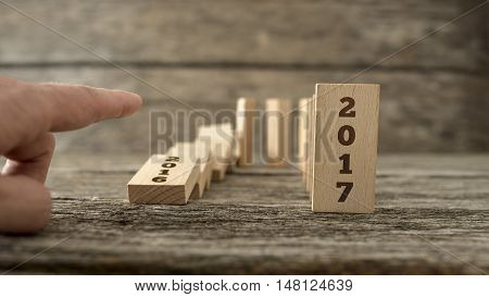 Man starting the domino effect from 2016 to 2017 knocking over the domino dated 2016 with his finger conceptual of the approaching New Year.