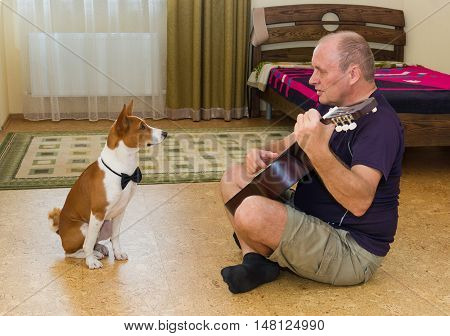Young dog and mature man composing music and playing guitar.
