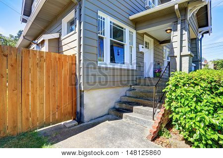 Concrete Floor Porch Of Siding House. Wooden Fence And Green Bushes