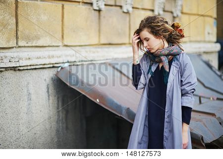 Tired young girl in colorful scarf and coat with dreadlocks in her hair standing in the courtyard of the house with his eyes closed.