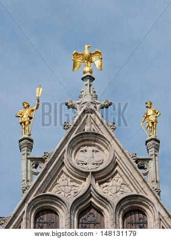 Detail of richly decorated Town Hall at the Great Square or Grote Markt in Antwerp, Belgium showing two golden statues and a golden eagle