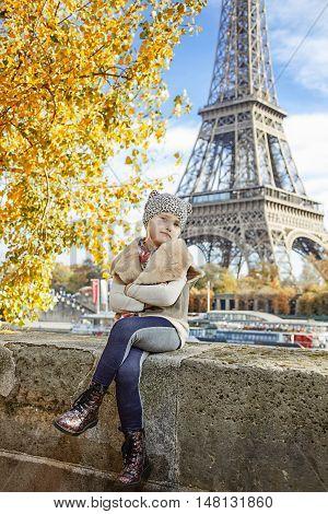 Elegant Girl On Embankment In Paris, France Sitting On Parapet