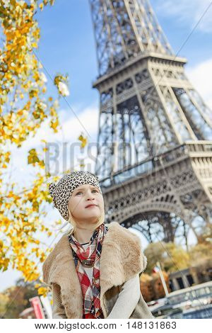 Girl Looking Into Distance While Sitting On Parapet In Paris