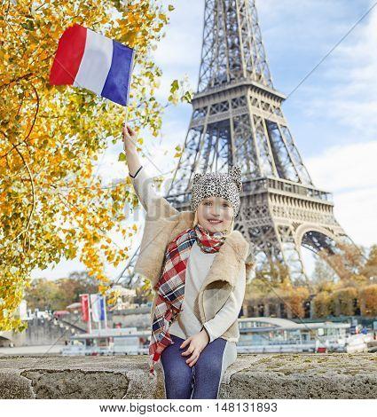 Elegant Child Rising Flag While Sitting On The Parapet In Paris