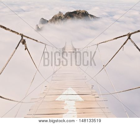 arrow on a rope bridge with wood planks in the sky