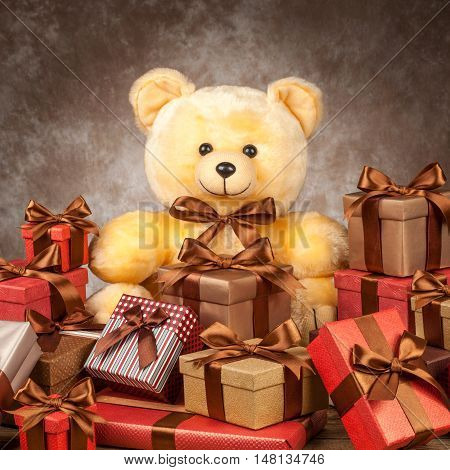 homemade teddy bear and a lot of boxes with gifts on the old board.