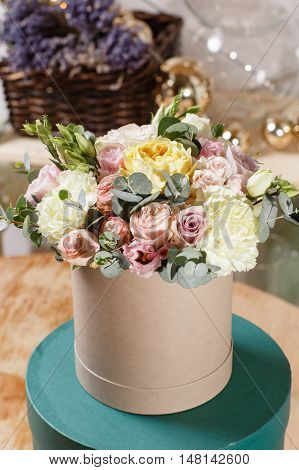 Rich bunch of composition in hatbox. A fresh bouquet of flowers of different colors mix.