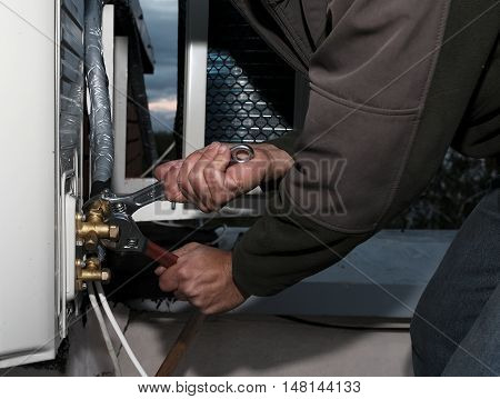 Master of repair air conditioners. Key to tighten the screws on the external unit