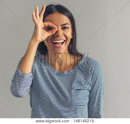 Beautiful young girl in casual clothes is showing Ok sign looking at camera and smiling on gray background