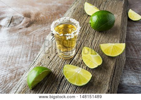 Tequila shot with lime slices on rustic wooden background. Strong alcohol drink. Gold Mexican tequila shot.