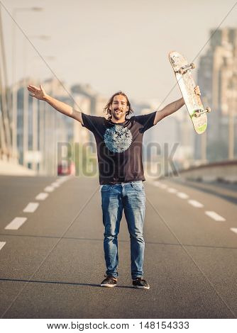 Happy Skateboarder Standing On The Road Bridge And Raising His Hands Up