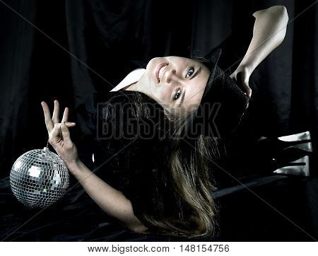 girl dancer with a mirror ball on dark background
