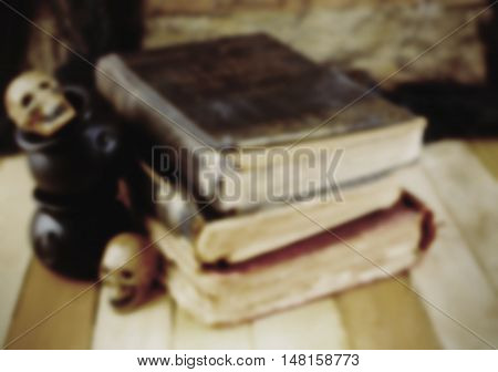 Background blur for Halloween in October includes old worn books miniature skulls and cauldrons on a wooden table. Low lighting used to enhance spooky vibe.