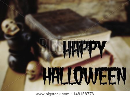 Background blur for Halloween in October includes old worn books miniature skulls and cauldrons on a wooden table. Low lighting used to enhance spooky vibe. Happy Halloween text added.