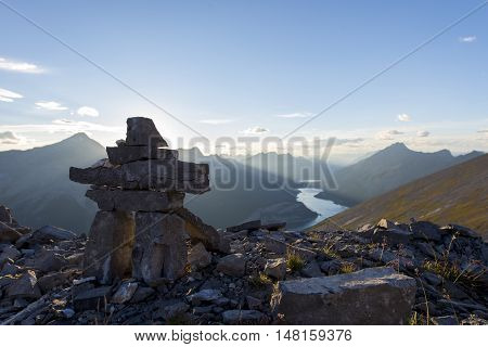 Inukshuk rock sculpture at the summit of a hiking trail in the rockies