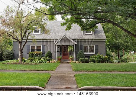 Gray Brick Cape Cod House on Overcast Day