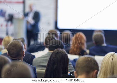 Male Host Presenting Repoer During the Conference. Speaking in Front of Large Group of People. Horizontal Image Composition