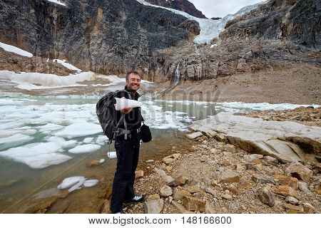 Man ecologist holding ice by a moraine lake.  Angel Glacier at Mount Edith Cavell. Jasper National Park. Canadian Rockies. Alberta. Canada.