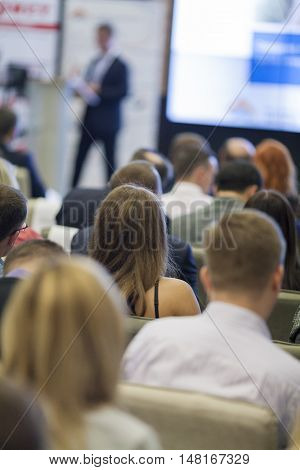 Large Group of People in Congress Hall Watching Presentation Charts on Board In Front.Vertical Image Orientation