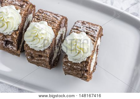 Detailed Top View On Chocolate Roulade Filled With Whipped Cream On White Tray