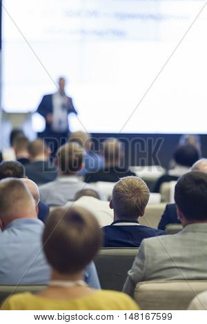 Business Ideas and Concepts. People at the Business Conference Listening to the Speaker Standing in Front of a Big Board on Stage.Vertical Image Orientation