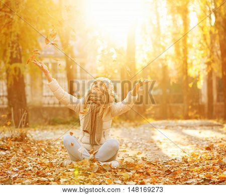 Portrait of a girl in the autumn park. Girl throws up fallen leaves. Autumn. The girl is wearing a knitted scarf and hat. Warm toning.
