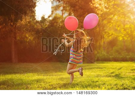 Little girl with balloons running on the lawn in the park outdoors. Freedom and carefree. Happy childhood. Man is unrecognizable.
