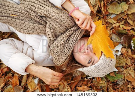 Portrait of a girl in the autumn park. Girl lying on fallen leaves and hides her face behind a maple leaf. Autumn. The girl is wearing a knitted scarf and hat.