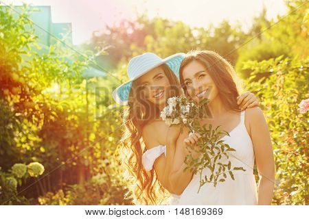 Two sisters. Girl holding a bouquet of flowers. Sister in the background embraces her. Family time. Human relationships.