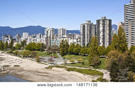Beautiful shot of Sunset Beach Park in front of the multitude of condominiums that line the popular beach front. Shot from the Burrard Bridge with the Rockies in the background on a gorgeous sunny day with blue skies. A row of trees line the street in fro