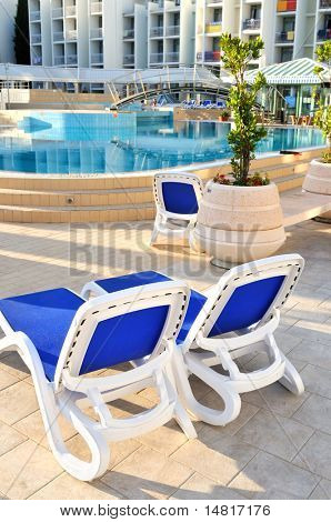 Empty chairs by the pool of luxury hotel