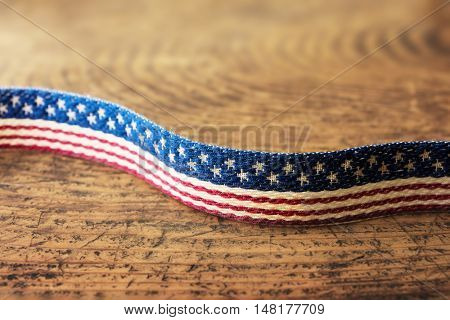 Background for American election or commemorative event. A textile with stars and stripes pattern on old rustic wooden table.
