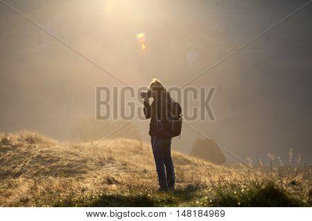 Photographer taking photos in autumn mountains in sunrise
