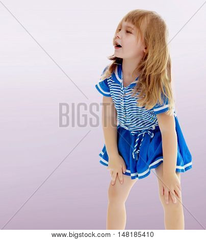 On a purple background, smooth transition from dark to light. Cute little unkempt girl in a short blue dress. Girl looking to the side with his hands on his knees.