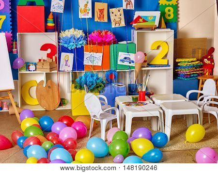 Interior of game room in preschool kindergarten. A lot of balloons on floor.