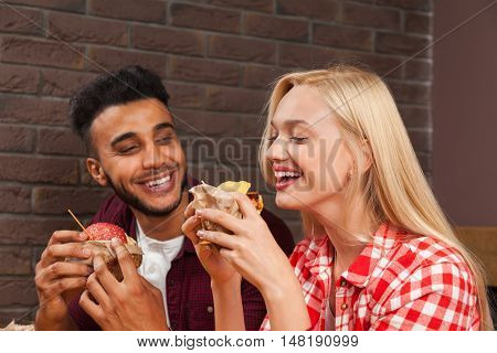 Young Man And Woman Eating Fast Food Burgers Sitting At Wooden Table In Cafe, Friends Meeting Communication