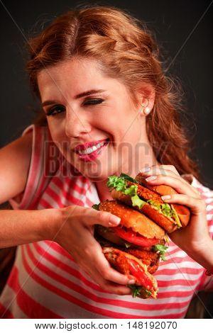 Girl keeps hamburger hamburger fast food. Hamburger is tasty fast food. Girl mischievously winking with one eye.