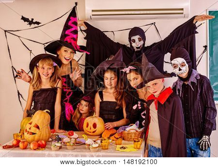 Halloween party with group children holding trick or treat in Halloween interior.Two adult in Halloween costume.