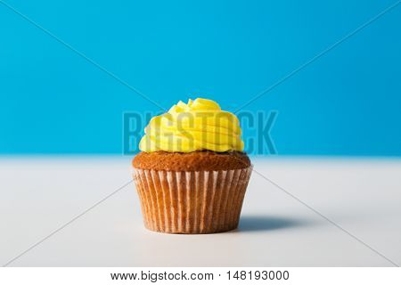 food, junk-food, culinary, baking and eating concept - close up of cupcake or muffin with icing on table